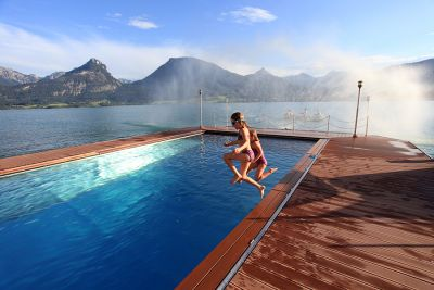 Two children jumping in the pool at Wolfgangsee in Austria